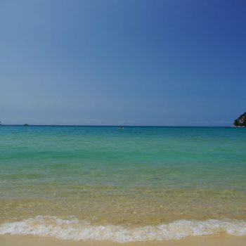 Het azuurblauwe water & het goudgele strand.