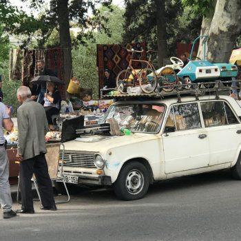 Een vlooienmarkt met een vol gezette auto