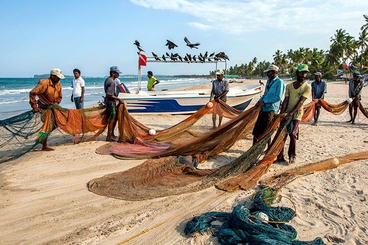 Vissers op het strand van Uppuveli